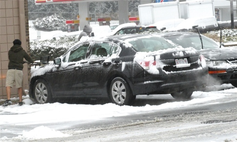 Man wearing shorts clearing snow from car, Gaithersburg, MD