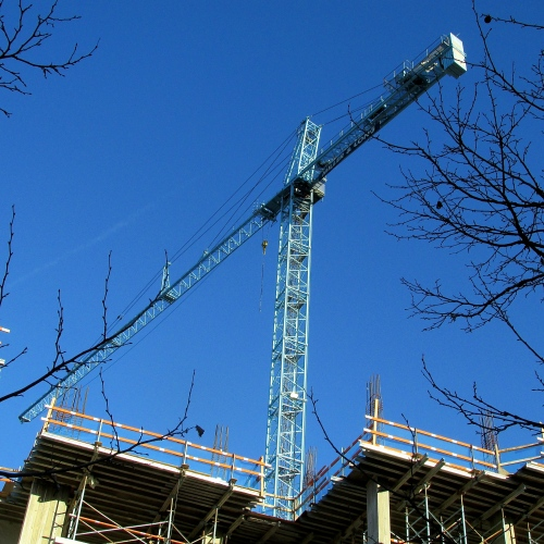A CONSTRUCTION CRANE TOWERS OVER A BUILDING IN PROGRESS IN THE HEART OF ROCKVILLE.